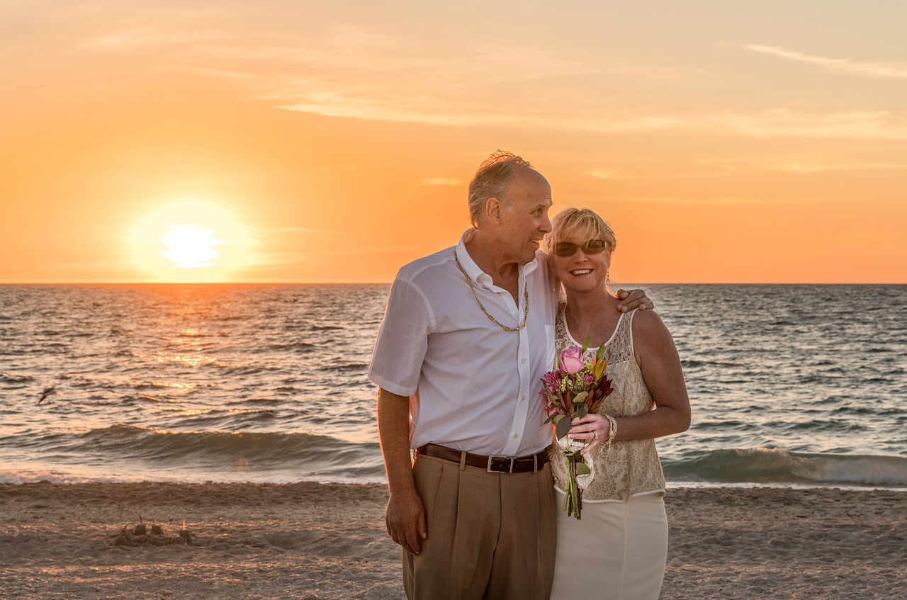 Elderly couple smiling on the beach at sunset