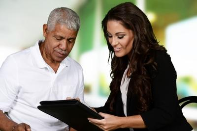 Young woman showing older man notebook