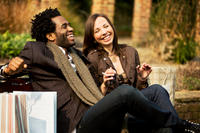 African american man and caucasian woman smiling and sitting on bench