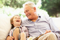 grandfather laughing with grandson in chair