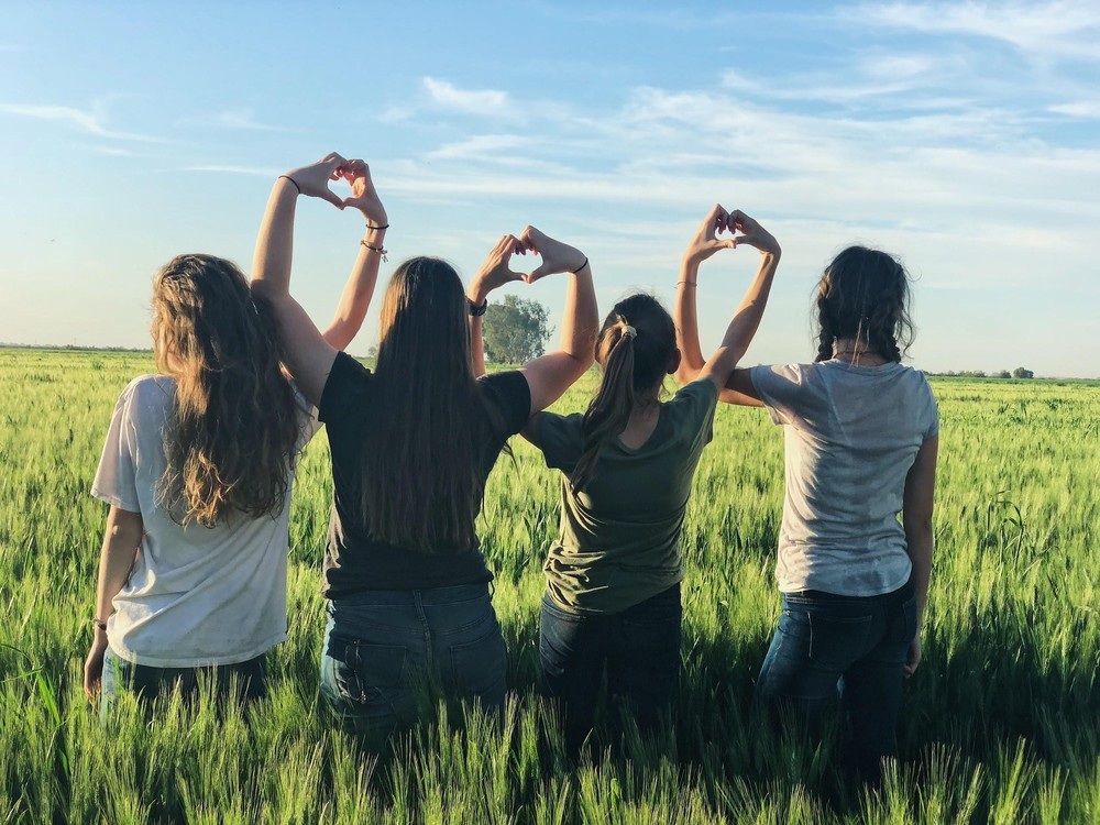 Four girls creating hearts with their hands together