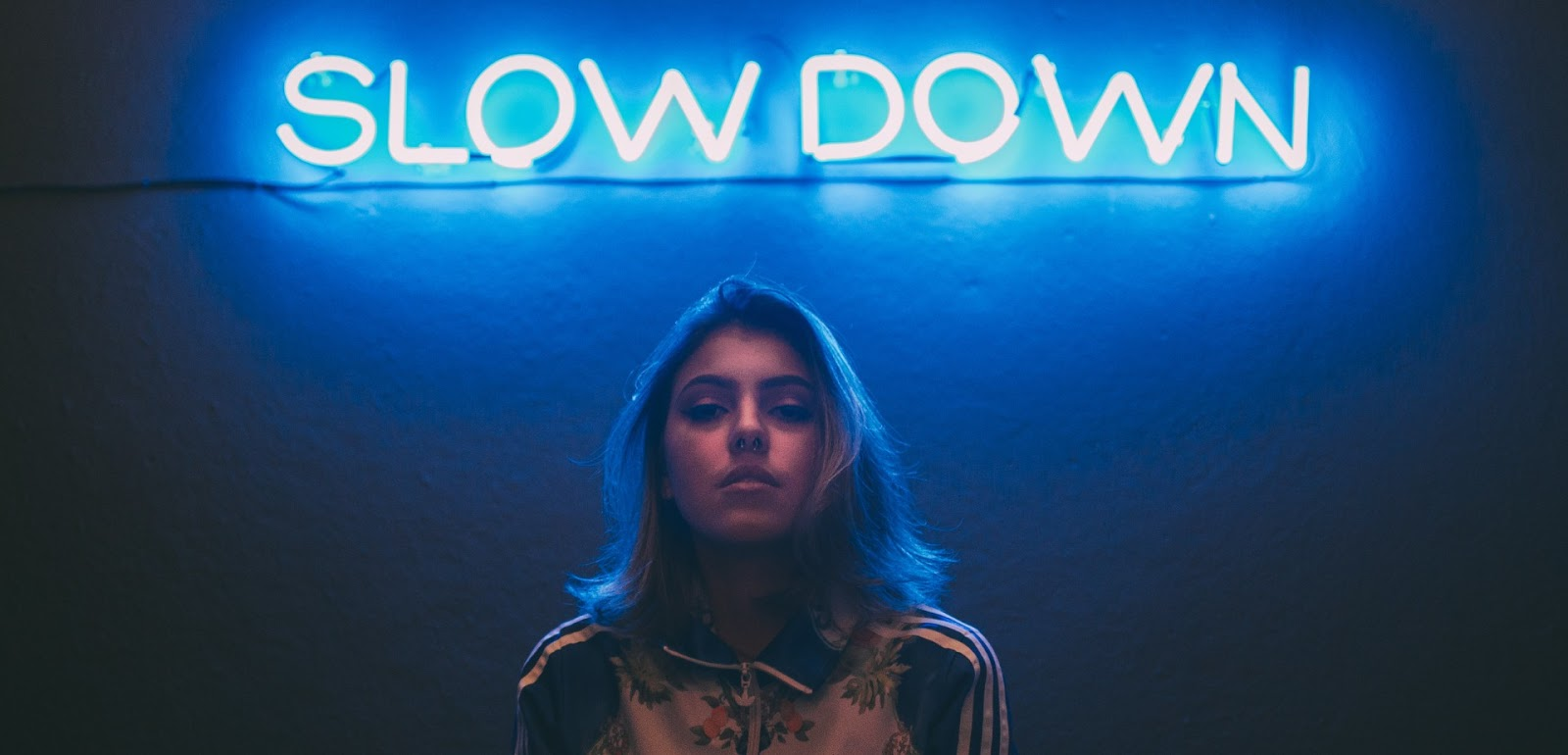 Girl with a glowing blue sign saying Slow Down