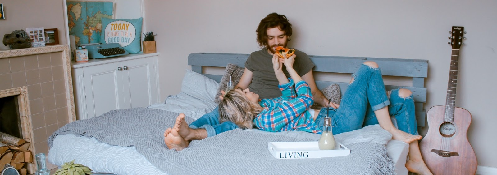 Man and woman eating snacks in bed
