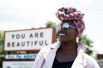 Beautiful woman standing in front of sign saying You are Beautiful